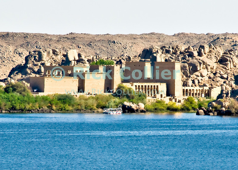 "Aswan, Egypt -- The Philae Temple was built on a small island just above the first cataracts in the Nile River.  The site of a temple dedicated to the cow god Hathor, this temple site was held sacred by both northern (Theban) and sourthern (Nubian) dynasties.  The temple complex as now viewed was actually built and used in the later Ptolemaic and subsequent Roman dynasties.  The original island location was submerged by the building of the Aswan High Dam, so the temple was relocated and is now visited on the island Agilika.  Before being relocated, the temple was partially submerged for many years, and a water line can be observed on some of the pylon walls. © Rick Collier / RickCollier.com.<br /> <br /> <br /> travel; vacation; tour; tourism; tourist; destination; Aswan; dam; ""Aswan dam""; ""High Dam""; Nile; river; ""Nile River""; Philae; ""Philae Temple""; Hathor; Ptolemy; Ptolemaic; Agilika; temple; hieroglyphic; hieroglyph; ""ancient Egypt"";"
