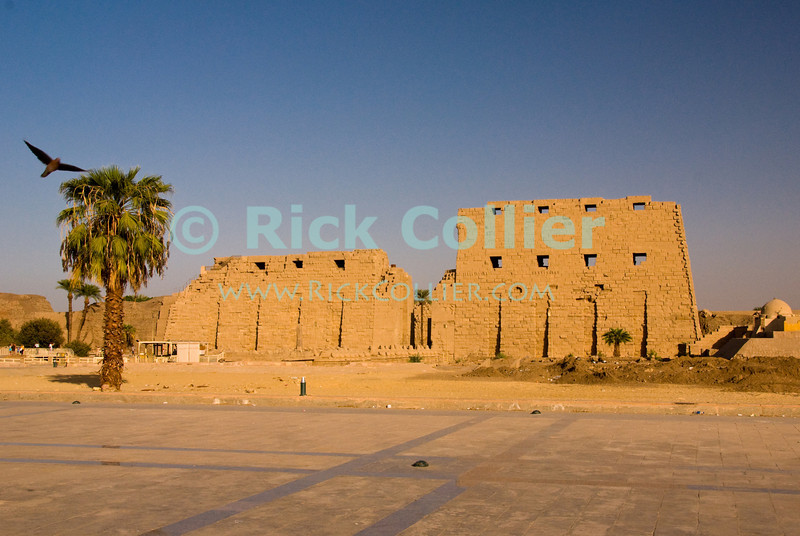 """Luxor, Egypt -- The first pylon of the ancient Egyptian temple of Karnak seems to glow in the orange evening sunlight.  Karnak was built over many generations of Egyptian pharoah, as each successive king added pieces to this temple honoring the most significant god of the ancient Egyptian pantheon, the god Amun (later, Amon-Ra), the sun god. © Rick Collier / RickCollier.com.<br /> <br /> <br /> <br /> <br /> <br /> travel; vacation; tour; tourism; tourist; destination; Egypt; Luxor; Karnak; """"Karnak Temple""""; Amun; Amon; Amon-Ra; temple; hieroglyph; hieroglyphic; """"ancient Egypt""""; archeology; archeological; ruin;"""