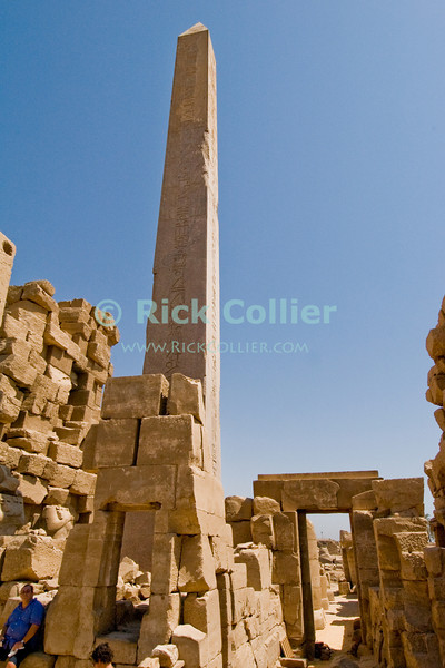 Karnak, outside Luxor, Egypt.  Hatshepsut's obelisk stands behind walls, between the fourth and fifth pylons at the great Temple of Amun (or Amon) in Karnak.  Hatshepsut's obelisks posed a dilemma in this sacred precinct.  Later pharoahs sought to eliminate all traces of Hatshepsut, but these obelisks could not be removed since they were dedicated to the supreme god.  The problem was solved by hiding them behind newer walls, thus hiding them from worshippers' sight without defiling them.  The home of Amon (the Sun God), Karnak was the center of Egyptian spiritual life during the middle and late kingdoms.  It was continuously being improved by successive pharoahs over a period of about 1300 years. © Rick Collier<br /> <br /> <br /> <br /> <br /> <br /> <br /> Egypt Egyptian Karnak Amon Amun tourist tourism history historic antiquity antiquities ruins temple tomb pylon wall column pillar ramp ancient 'ancient Egypt' Hatshepsut obelisk Thebes Theban Thebian