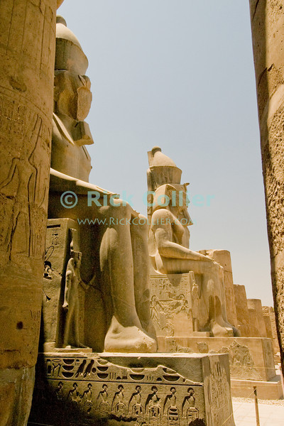 Luxor Temple, Egypt.  Enormous statues (colussi) of Ramses II enthroned guard the entrance to the Colonnaded court at the second pylon within the temple.  © Rick Collier<br /> <br /> <br /> <br /> <br /> <br /> <br /> Egypt Egyptian Karnak Luxor Amon Amun tourist tourism history historic antiquity antiquities ruins temple tomb pylon wall column pillar ramp ancient 'ancient Egypt' Thebes Theban Thebian Mut Konsu Amun-Min Khonsu carving Ramses 'Ramses II' statue colossus colossi