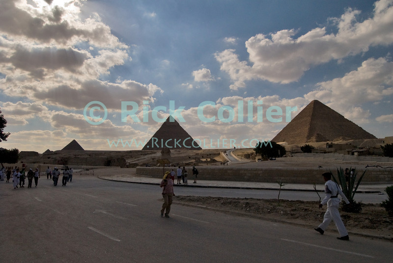 """Giza, Cairo, Egypt -- Tourists leave the pyramids complex at the end of a hot day at Giza. © Rick Collier / RickCollier.com<br /> <br /> <br /> <br /> <br /> <br /> travel; vacation; destination; Egypt; Cairo; Giza; pyramids; pyramid; """"Pyramids at Giza""""; tourist; tourism; desert; panorama; view; Cheops; Khufu; Khafre; Kephren; Menkaure; Mykerinus; """"queen's pyramids""""; sphinx; """"Great Sphinx""""; necropolis; temple; """"funerary temple"""";"""