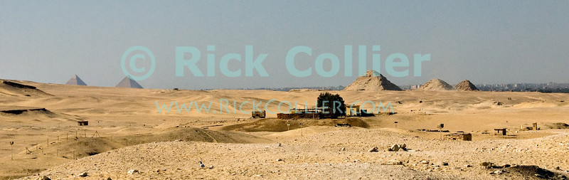 """Saqqara, Cairo, Egypt -- There are hundreds of pyramids in Egypt.  Many are easily visible all around the famous step pyramid of Djoser (Dozer).  (The impressive and famous pyramids at Giza are visible on the left of this panorama, with Cairo in the distant background.) © Rick Collier / RickCollier.com.<br /> <br /> <br /> <br /> <br /> <br /> travel; vacation; tour; tourism; tourist; destination; Egypt; Cairo; Saqqara; Djoser; Dozer; pyramid; """"step pyramid""""; pyramids; """"Great Pyramid""""; Giza; desert; view; panorama;"""