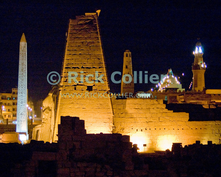 After dark spectacular lighting makes it easier to pick out the obelisk and statues of Ramses II in front of the first pylon (outer gate), with the lit mosque just behind the wall atop Luxor Temple, Egypt.  Dedicated to the Theban triad of Amun-Min, Mut, and Konsu, Luxor Temple standing in the center of town is lit up at night.  © Rick Collier<br /> <br /> <br /> <br /> <br /> <br /> <br /> Egypt Egyptian Karnak Luxor Amon Amun tourist tourism history historic antiquity antiquities ruins temple tomb pylon wall column pillar ramp ancient 'ancient Egypt' Thebes Theban Thebian Mut Konsu Amun-Min Khonsu obelisk pylon wall Ramses 'Ramses II' statue colossus colossi night illumination lights dark 'after dark' nighttime