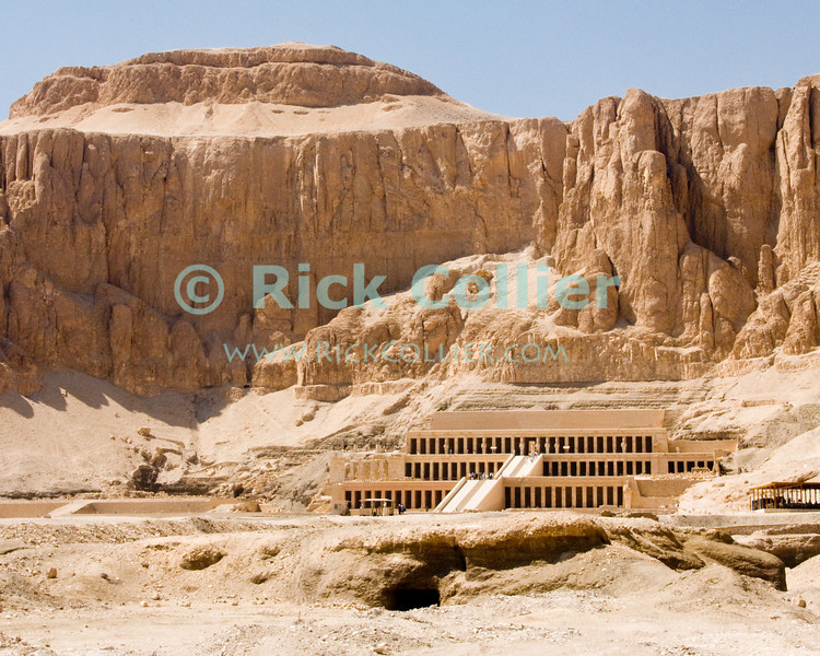 """Luxor, Egypt -- The funerary temple of Hatshepsut, cut into the cliffs at the west edge of the Nile River valley at Deir el-Bahri, near the Valley of the Kings.  Hatshepsut famously was the queen who ruled Egypt as a king (male) and may have heretically had herself burried as Pharoah in the Valley of the Kings.  Subsequent pharoahs tried to obliterate evidence and monuments to Hatshepsut (beginning possibly from the reign of Thutmos III, several years after Hatshepsut's death and entombment). © Rick Collier / RickCollier.com.<br /> <br /> <br /> <br /> <br /> <br /> travel; vacation; tour; tourism; tourist; destination; Egypt; Luxor; valley; """"Valley of the Dead""""; """"Valley of the Kings""""; kings; pharoah; pharoahs; tomb; temple; """"ancient Egypt""""; tombs; excavation; excavations; archaeology; Hatshepsut; """"Hatshepsut Temple""""; """"Deir el-Bahri""""; """"Dar el-Bahri"""""""
