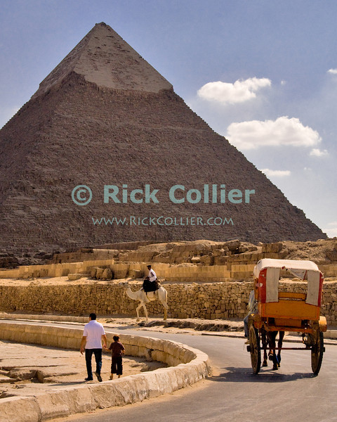 """Giza, Cairo, Egypt -- Tourists wander around the pyramids under the watchful eye of a Tourism and Antiquities policeman on camel.  (The """"second"""" pyramid of Khafre [Kephren] is in the background). © Rick Collier / RickCollier.com<br /> <br /> <br /> <br /> <br /> <br /> travel; vacation; destination; Egypt; Cairo; Giza; pyramids; pyramid; """"Pyramids at Giza""""; Khafre; Kephren; Chefren; """"horse-drawn carriage""""; cart; carriage; horse; police; camel; tourist; tourism"""