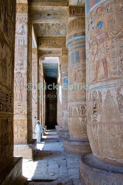 Medinet Habu -- the Mortuary Temple of Ramses III, near Luxor, Egypt.  Tour guides and local Egyptians wait in the shade for opportunities to earn a few pounds by helping tourists.  The temple is remarkable for its excellent state of preservation and extremely deep heiroglyphic carvings.  The original paint and coloration in many parts has been protected by the very deep carvings and solid construction, so still shows in many parts.  The heaviness of construction and depth of carvings was considered a sign of the pharoah's great importance and wealth.  © Rick Collier<br /> <br /> <br /> <br /> <br /> <br /> <br /> Egypt Egyptian Habu 'Medinet Habu' Luxor tourist tourism history historic antiquity antiquities Thebes Theban Thebian Nile 'Nile River' temple tomb monument souvenir shop town village 'Valley of the Kings' necropolis Ramses 'Ramses III' heiroglyph heiroglyphic painting decoration guide tour arab
