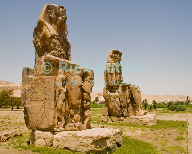 """The Colossi of Memnon.  These were originally constructed as statues flanking the entrance to the mortuary temple of Amenophis III, but the temple was subsequently plundered by later pharoahs so nothing remains.  Later fractured by an earthquake, in Greek and Roman times these statues were occasionally heard to """"sing"""" when the breeze would rise at dawn.  The statues were subsequently repaired at the orders of Roman emperor Septimus Severus in 199 AD. © Rick Collier<br /> <br /> <br /> <br /> <br /> <br /> <br /> Egypt Egyptian Habu 'Medinet Habu' Luxor tourist tourism history historic antiquity antiquities Thebes Theban Thebian Nile 'Nile River' temple tomb monument souvenir shop town village 'Valley of the Kings' necropolis Memnon colossus colossi 'Colossi of Memnon' Amenophis 'Amenophis III'"""