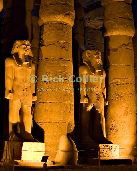 """Luxor, Egypt -- Statues of Ramses II alternate with columns in the Peristyle courtyard inside Luxor Temple.  Luxor Temple was built principally by two pharoahs, Ramses II and Amenhotep III, and was the companion temple to Karnak for worship of the Theban triad of gods, Amun, his wife Mut, and their son Khonsu. While Karnak was the home of Amun, his wife Mut and son Khonsu resided at Luxor.  The two temples were linked by a road lined with sphinxes, the end of which is now visible at the approach to Luxor Temple. © Rick Collier / RickCollier.com.<br /> <br /> <br /> <br /> <br /> <br /> travel; vacation; tour; tourism; tourist; destination; Egypt; Luxor; temple; hieroglyph; hieroglyphic; """"ancient Egypt""""; archeology; archeological; ruin; sphinx; """"Luxor Temple""""; Amenhotep; """"Ramses II""""; statue; figure; column;"""