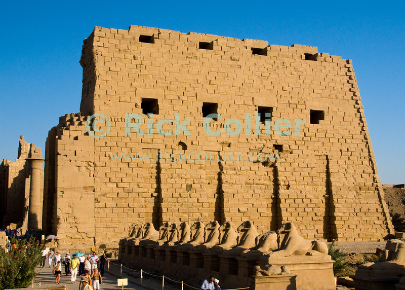 """Luxor, Egypt -- A row of ram-headed sphinxes lines the approach to the first pylon of the ancient Egyptian temple of Karnak.  The temple seems to glow in the orange evening sunlight.  Karnak was built over many generations of Egyptian pharoah, as each successive king added pieces to this temple honoring the most significant god of the ancient Egyptian pantheon, the god Amun (later, Amon-Ra), the sun god. © Rick Collier / RickCollier.com.<br /> <br /> <br /> <br /> <br /> <br /> travel; vacation; tour; tourism; tourist; destination; Egypt; Luxor; Karnak; """"Karnak Temple""""; Amun; Amon; Amon-Ra; temple; hieroglyph; hieroglyphic; """"ancient Egypt""""; archeology; archeological; ruin;"""