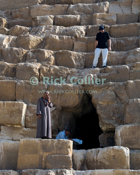 """Giza, Cairo, Egypt -- A tourist looks down from above on local staff attending their daily routines on the Great Pyramid of Khufu (Cheops) at Giza. © Rick Collier / RickCollier.com<br /> <br /> <br /> <br /> <br /> <br /> travel; vacation; destination; Egypt; Cairo; Giza; pyramids; pyramid; """"Pyramids at Giza""""; tourist; tourism; Cheops; Khufu"""