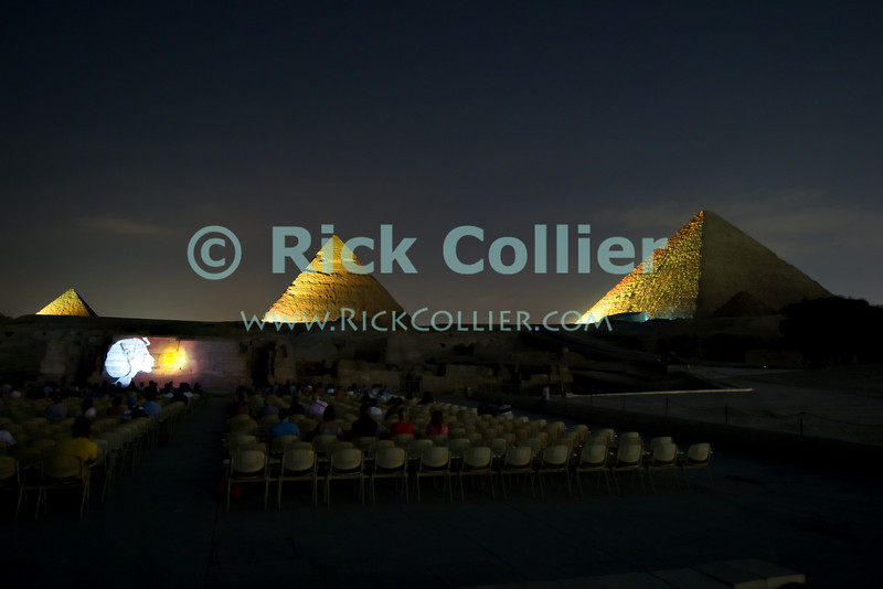 """Giza, Cairo, Egypt -- The three famous pyramids at Giza, surrounded by the """"queen's pyramids"""" and with the remains of the funerary temple of Khafre (Khephren) (featuring the Great Sphinx) are spectacularly illuminated during the famous sound and light show at Giza. © Rick Collier / RickCollier.com<br /> <br /> <br /> <br /> <br /> <br /> travel; vacation; destination; Egypt; Cairo; Giza; pyramids; """"Pyramids at Giza""""; Cheops; Khufu; Khafre; Kephren; Chephren; Menkaure; Mykerinus; """"Queen's pyramid""""; Sphinx; """"Great Pyramid""""; """"Great Sphinx""""; necropolis; temple; temples; light; night; """"light show""""; """"sound and light""""; show; presentation"""