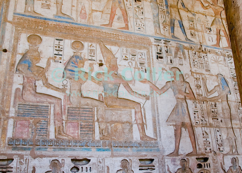 Medinet Habu -- the Mortuary Temple of Ramses III, near Luxor, Egypt.  Remarkable for its excellent state of preservation and extremely deep heiroglyphic carvings, the original paint and coloration in many parts has been protected by the very deep carvings and solid construction, so still shows in many parts.  The heaviness of construction and depth of carvings was considered a sign of the pharoah's great importance and wealth.  © Rick Collier<br /> <br /> <br /> <br /> <br /> <br /> <br /> Egypt Egyptian Habu 'Medinet Habu' Luxor tourist tourism history historic antiquity antiquities Thebes Theban Thebian Nile 'Nile River' temple tomb monument souvenir shop town village 'Valley of the Kings' necropolis Ramses 'Ramses III' heiroglyph heiroglyphic painting decoration anhk cartouche