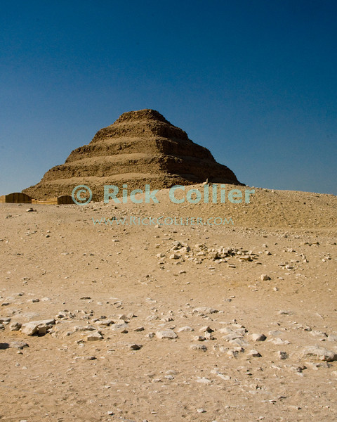 """Saqqara, Cairo, Egypt -- The famous step pyramid of Djoser (Dozer) stands above the desert sand at Saqqara. © Rick Collier / RickCollier.com.<br /> <br /> <br /> <br /> <br /> <br /> travel; vacation; tour; tourism; tourist; destination; Egypt; Cairo; Saqqara; Djoser; Dozer; pyramid; """"step pyramid"""";"""
