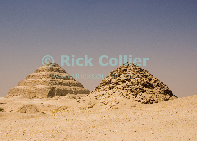 The desert at Saqqara, Egypt, is dotted with pyramids.  Here a much newer pyramid that has begun to collapse stands in the foreground, with the famous 'Step Pyramid of Zoser (or Djoser, or Doser) in the background.  Zoser's pyramid is among the oldest pyramids in Egypt, was designed and built by Imhotep, who was the pharoe's architect.  The 'step pyramid' style predates the more famous smooth-sided pyramids found in Giza. © Rick Collier<br /> <br /> <br /> <br /> <br /> <br /> <br /> Egypt Egyptian Cairo Saqqara pyramid pyramids step steps pharoah pharoahs Zoser Dozer Doser Djoser 'step pyramid' Imhotep tourist tourism history historic antiquities 'ancient Egypt' ancient antiquity audience tomb tombs