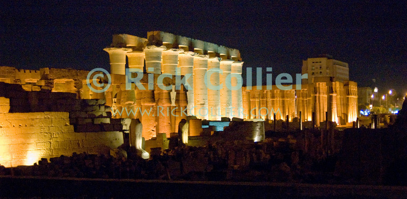 Luxor Temple, Egypt, makes a spectacular scene, dominating the town when illuminated at night.  Dedicated to the Theban triad of Amun-Min, Mut, and Konsu, Luxor Temple standing in the center of town is lit up at night.  © Rick Collier<br /> <br /> <br /> <br /> <br /> <br /> <br /> Egypt Egyptian Karnak Luxor Amon Amun tourist tourism history historic antiquity antiquities ruins temple tomb pylon wall column pillar ramp ancient 'ancient Egypt' Thebes Theban Thebian Mut Konsu Amun-Min Khonsu obelisk pylon wall Ramses 'Ramses II' statue colossus colossi night illumination lights dark 'after dark' nighttime