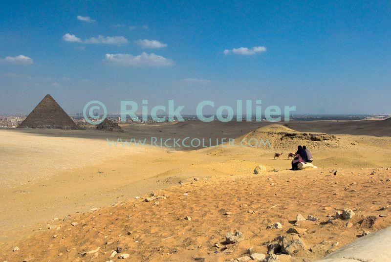 """Giza, Cairo, Egypt -- Tourists enjoy the panoramic view of the pyramids and Cairo from the overlook site at Giza. © Rick Collier / RickCollier.com<br /> <br /> <br /> <br /> <br /> <br /> travel; vacation; destination; Egypt; Cairo; Giza; pyramids; pyramid; """"Pyramids at Giza""""; tourist; tourism; camel; ride; """"camel ride""""; """"camel caravan""""; desert; panorama; view; Cheops; Khufu; Khafre; Kephren; Menkaure; Mykerinus; """"queen's pyramids"""""""