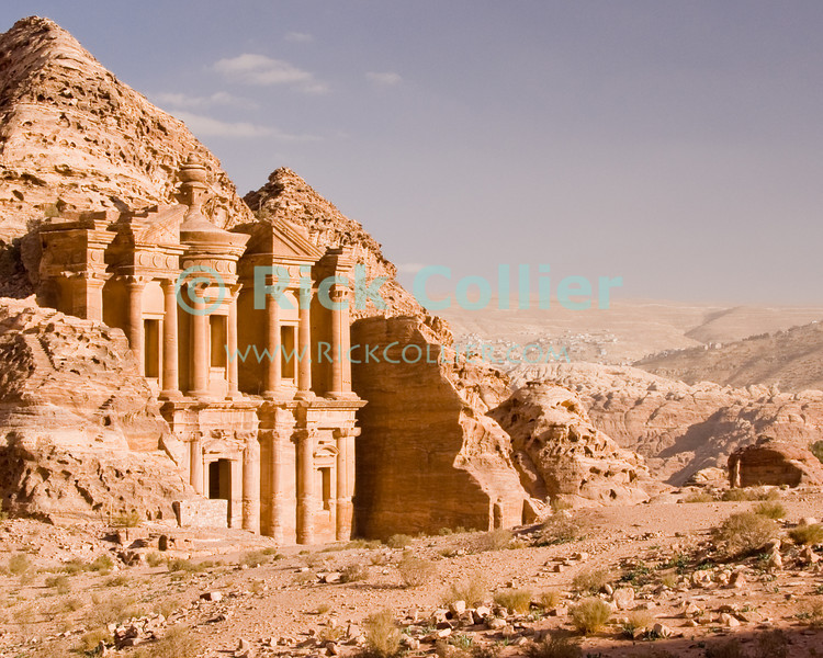 "The modern town of Wadi Musa is visible in the hills beyond Petra, overshadowed by the massive ""monestary"" at the overlook points at the back of Petra.  © Rick Collier<br /> <br /> <br /> <br /> Jordan Petra Nabatea Nabatean Rome Roman ruin archeology 'ancient world' antiquity cave 'cave dwelling' antiquities Bible Biblical civilization history historic desert stone cliff wall carve carved facade tourist tourism archeology tomb tombs valley desert necropolis monestary 'ad-Deir arab town village 'Wadi Musa'"