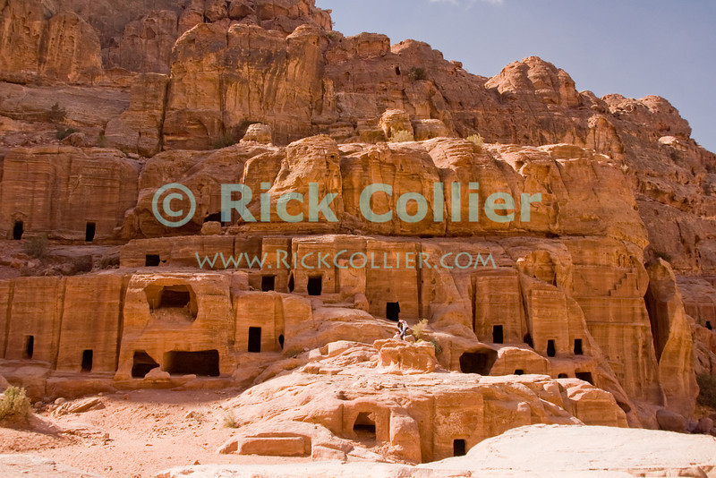 """""""Street of Facades,"""" Petra, Jordan.  Layer upon layer of Nabatean tombs carved by hand from the rock wall of the valley, at the so-called """"Street of Facades"""" or necropolis near the entrance to Petra.  © Rick Collier<br /> <br /> <br /> <br /> Jordan Petra Nabatea Nabatean ruin archeology 'ancient world' antiquity cave 'cave dwelling' antiquities Bible Biblical civilization history historic desert stone cliff wall carve carved facade tourist tourism archeology tomb tombs valley block blocks desert necropolis"""