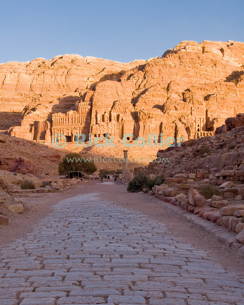 "Petra, Jordan -- The ancient Roman ""Colonnaded Street"" (""Cardo Maximus"") seems to lead directly to the most impressive Nabatean ""royal tombs,"" with the ""Palace Tomb"" on the left.  © Rick Collier<br /> <br /> <br /> <br /> Jordan Petra Nabatea Nabatean Rome Roman ruin archeology 'ancient world' antiquity cave 'cave dwelling' antiquities Bible Biblical civilization history historic desert stone cliff wall carve carved facade tourist tourism archeology tomb tombs valley path road hike trail desert necropolis 'Colonnaded Street' street road cobblestone 'Cardo Maximus' royal"