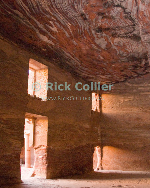 """Inside the """"Urn Tomb,"""" Petra, Jordan.  The ceiling and walls of this hand-carved space reveal the fantastic grain of the natural sandstone rock from which it was carved.  © Rick Collier<br /> <br /> <br /> <br /> Jordan Petra Nabatea Nabatean Rome Roman ruin archeology 'ancient world' antiquity cave 'cave dwelling' antiquities Bible Biblical civilization history historic desert stone cliff wall carve carved facade tourist tourism archeology royal tomb tombs valley desert necropolis street road 'Urn Tomb' interior window door sunlight sandstone rock grain"""
