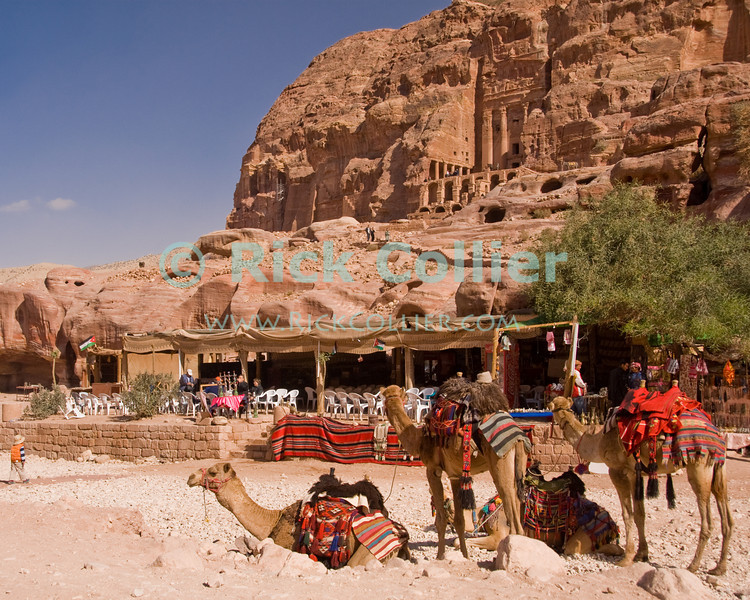 """A restaurant sits in the shadow of the famous """"urn tomb"""", visible high on the rock wall at the Nabatean capital of Petra, Jordan.  © Rick Collier<br /> <br /> <br /> <br /> Jordan Petra Nabatea Nabatean ruin archeology 'ancient world' antiquity cave 'cave dwelling' antiquities Bible Biblical civilization history historic desert rock stone cliff wall carve carved facade valley tourist tourism archeology tomb tombs valley block blocks camel camels desert necropolis"""