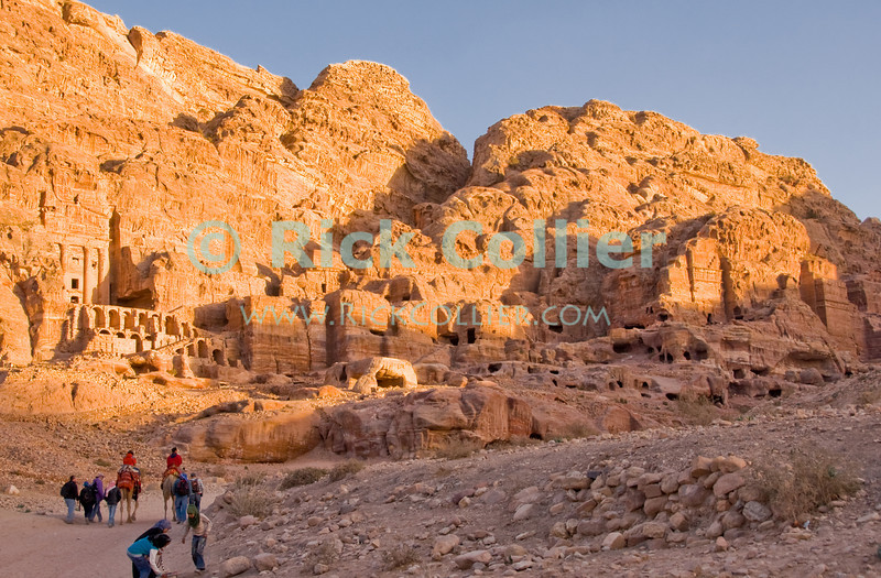 """Petra, Jordan.  The setting sun lights up the famous """"Urn Tomb"""" (left side) and reveals many levels of residences and tombs cut into the rock valley walls.  © Rick Collier<br /> <br /> <br /> <br /> Jordan Petra Nabatea Nabatean Rome Roman ruin archeology 'ancient world' antiquity cave 'cave dwelling' antiquities Bible Biblical civilization history historic desert stone cliff wall carve carved facade tourist tourism archeology royal tomb tombs valley path road hike trail desert necropolis street road 'Urn Tomb'"""