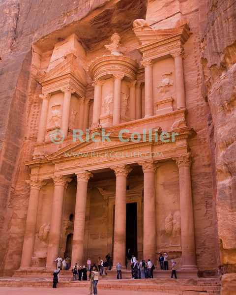 """""""The Treasury,"""" Petra.  The first """"structure"""" encountered after emerging from the Siq into the Nabatean ruins at Petra.  Carved completely by hand from the rock, this structure was probably actually a tomb.  It was dubbed """"the treasury"""" due to a rumor that the Pharoah's gold was hidden in the carved """"urn"""" shape at the top of this facade.  © Rick Collier<br /> <br /> <br /> <br /> Jordan Petra Nabatea Nabatean ruin archeology 'ancient world' antiquity cave 'cave dwelling' antiquities Bible Biblical civilization history historic desert stone cliff wall carve carved facade tourist tourism archeology royal tomb tombs treasury"""