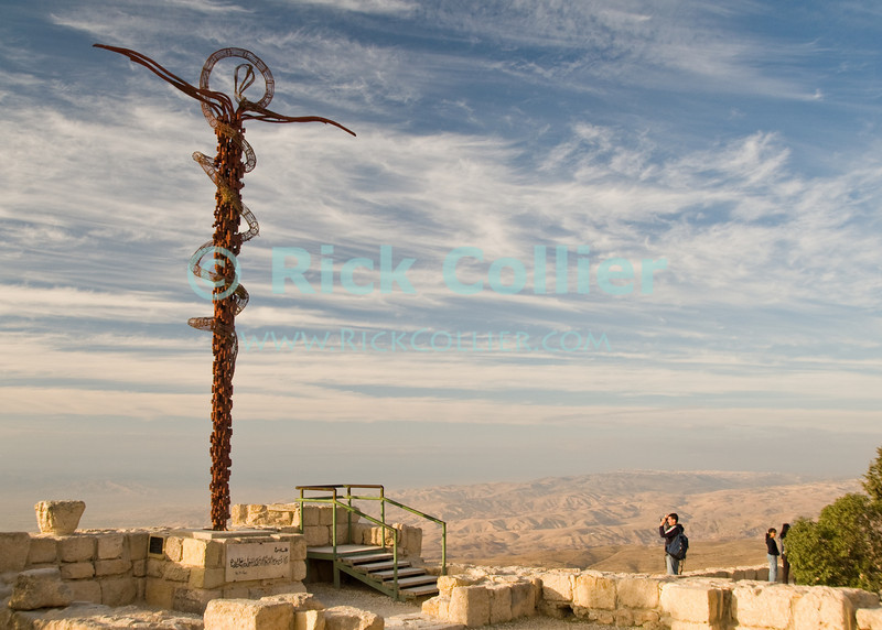 """A stylized """"Jesus crucified"""" overlooks the view of the Promised Land (now Israel), as Moses must have seen it at the top of Mt. Nebo, Jordan. © Rick Collier<br /> <br /> <br /> <br /> <br /> Jordan 'Mount Nebo' 'Mt. Nebo' Nebo church Bible Biblical Roman history historic archaeology 'Holy land' Christian 'Old Testament' 'holy place' antiquities antiquity cross chapel altar mosaic Moses 'Church of Moses' 'Promised Land' cross crucifix monument view panorama tourist tourism Israel Galilee"""