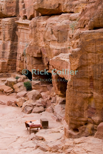 """""""Office Space""""  -- A table and chest mark a bedouin's usual place of business, where the owner can rest in the carved spaces created by the Nabateans in the Wadi ad-Deir, at the back of Petra. © Rick Collier<br /> <br /> <br /> <br /> Jordan Petra Nabatea Nabatean Rome Roman ruin archeology 'ancient world' antiquity cave 'cave dwelling' antiquities Bible Biblical civilization history historic desert stone cliff wall carve carved facade tourist tourism archeology tomb tombs valley path road hike trail desert necropolis steps stairs arab bedouin vendor table desk chest office space"""