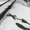 Railside sign shadows on snow.