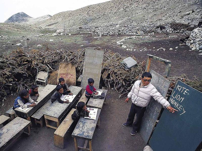 Lama La teaches outside his home in a makeshift school at Muguthang