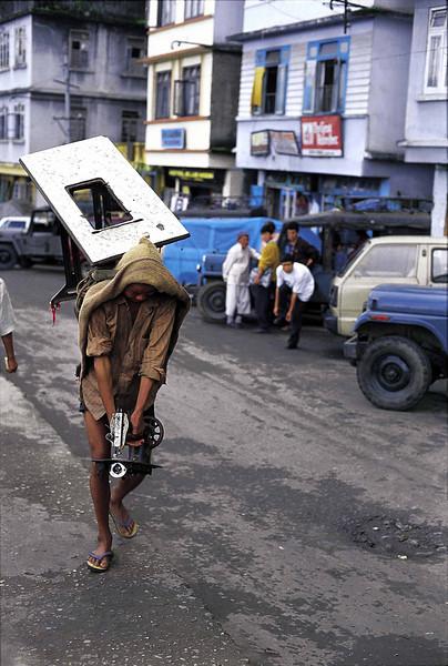 A porter carries a sewing machine along a Gangtok street
