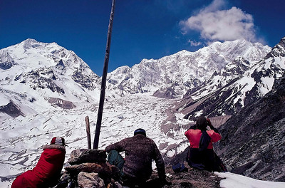 Major General Kukreti examines the north east face of Kangchendzonga during the Assam Rifles expedition in May 1987 from a high point above the Green Lakes Base Camp. The long north east ridge culminates in the Zemu Gap. The peak on the left is Simvu with the Zemu Glacier below.