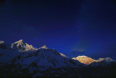 Siniolchu (left) and  Kangchendzonga (right),  guardian deity of the Sikkimese,  greets a  frosty dawn at  Rest Camp before Green Lakes, the base camp of the mountain at an altitude of around 5000 metres on the Zemu Glacier. Both revered and feared by the Sikkimese,  the mountain was first climbed by a British team in 1955 who in deference to the wishes of the Chogyal ( ruler) of Sikkim did not set foot on the holy summit.