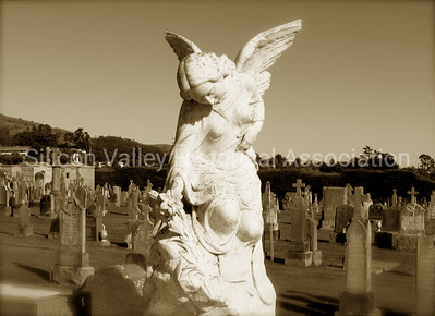 Statue of an angel holding a lily at the Italian Cemetery in Colma, California