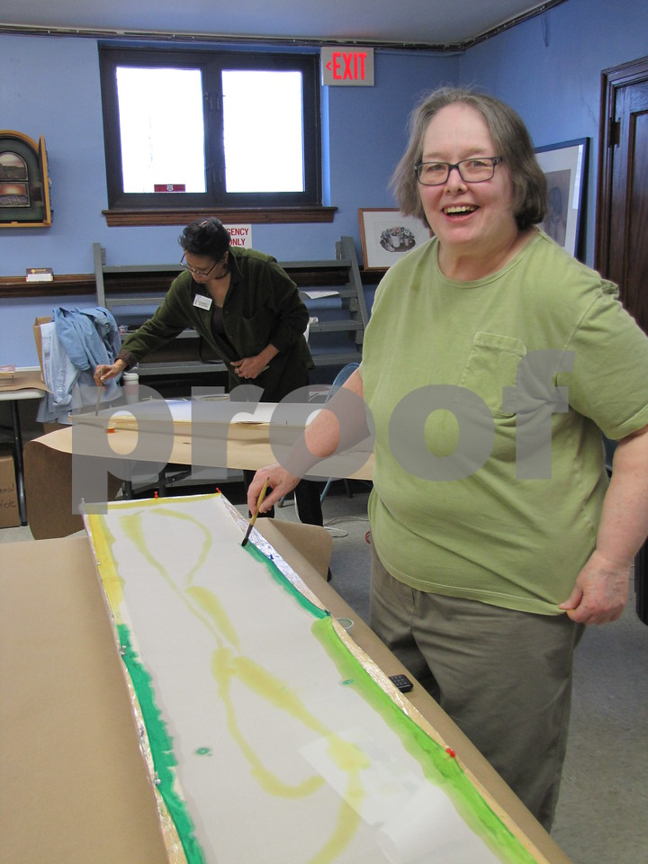 Deb Nerness applies paint to a scarf in the silk painting class held at the Blanden.