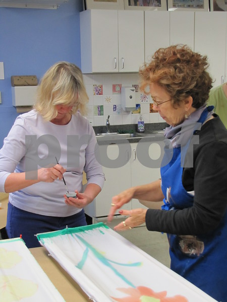 Mary Vollmer receiving some instruction from artist Pam Sanders.