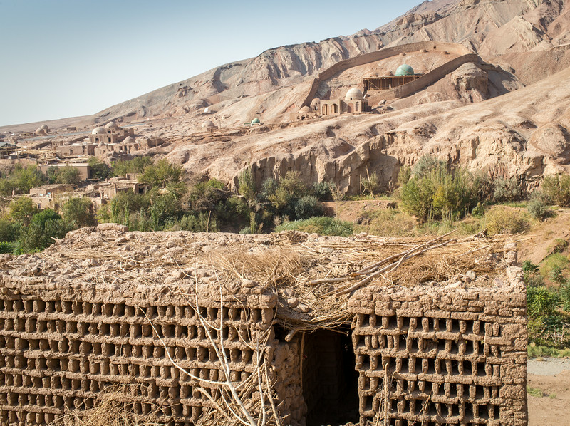 """Tuyuk Village, Turpan, China: On the other side of the Flaming Mountains from Turpan, this small village is called """"Little Mecca"""" because five visits to the mosque in the background is considered equivalent to the once-in-a-lifetime Mecca hajj to which most Muslims aspire. In the foreground is a raisin drying hut."""