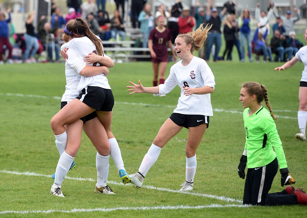 . Alexa Karsel (12) of Silver Creek, scores the winning goal past Morgan Palermo, right, of Ponderosa. Colleen Tyrrell comes from the left for a hug, while Kate Eggen, comes from the right. Silver Creek beats Ponderosa 2-1 in overtime in Longmont on Saturday. For more photos, go to dailycamera.com.  Cliff Grassmick / Staff Photographer/ May 12, 2018