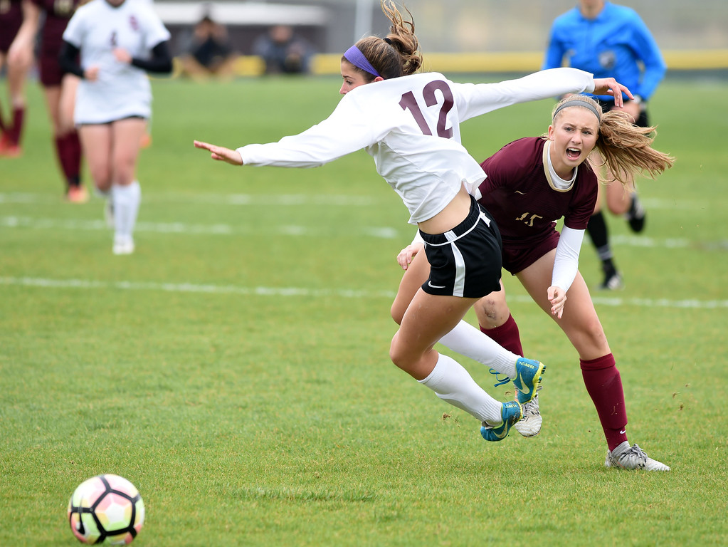 . Emma Everts, right, of Ponderosa, trips up Alexa Karsel, of Silver Creek. Silver Creek beats Ponderosa 2-1 in overtime in Longmont on Saturday. For more photos, go to dailycamera.com.  Cliff Grassmick / Staff Photographer/ May 12, 2018