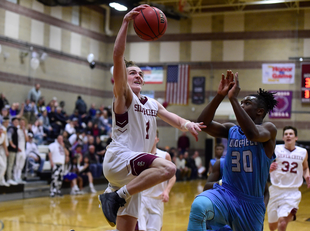 . Silver Creek High School\'s Nick Eaton goes for a layup over Randall Days during a Sweet 16 playoff game against Widefield on Wednesday in Longmont. Widefield won the game 54-51. More photos: BoCoPreps.com Jeremy Papasso/ Staff Photographer 02/28/2018