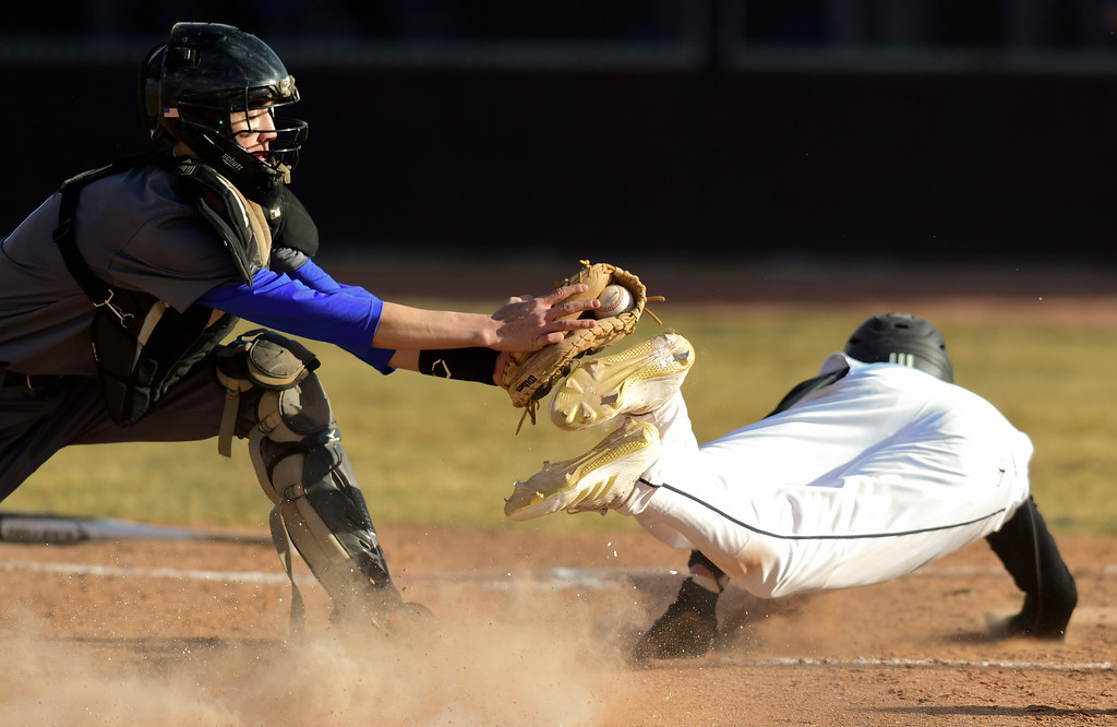 . Broomfield High School\'s Caleb Eiguren (No. 5) tags out Silver Creek High School\'s Travis Bicknell  (No. 6) in Longmont, Colorado on March 12, 2018. (Photo by Matthew Jonas/Staff Photographer)