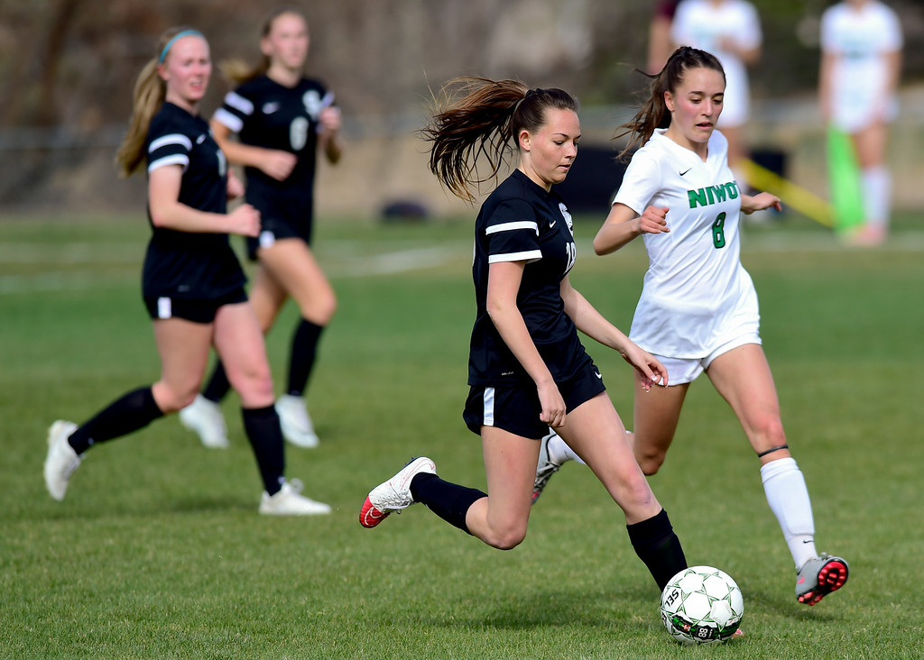 . Niwot High School\'s Elise Crall (No. 8) puts pressure on Silver Creek High School\'s Nadia Ziegler (No. 18) in Niwot, Colorado on April 10, 2018. (Photo by Matthew Jonas/Staff Photographer)