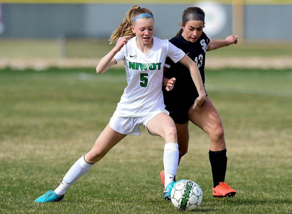 . Niwot High School\'s Kiera Flanagan (No. 5) and Silver Creek High School\'s Mallory Lopez (No. 13) chase after the ball in Niwot, Colorado on April 10, 2018. (Photo by Matthew Jonas/Staff Photographer)