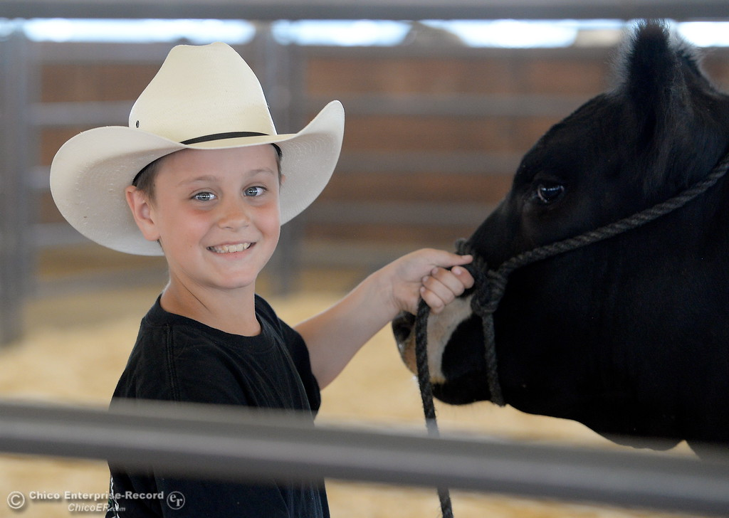 . 10-year-old Orion Helberg smiles with his steer that he calls Octomus Prime as things get underway at the Silver Dollar Fairgrounds in Chico, Calif. Tues. May 22, 2018.  (Bill Husa -- Photos)