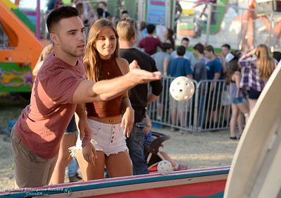 Justin Collins of Chico tries to win something for Alyssa Yakel at the Bank A Ball game at the Silver Dollar Fair in Chico, Calif. Friday May 27, 2016. (Bill Husa -- Enterprise-Record)