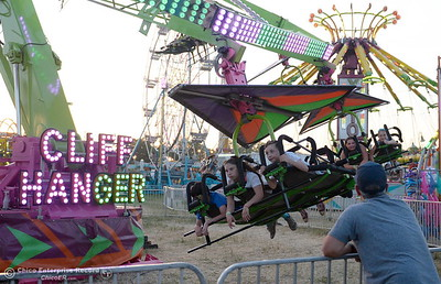 At right, Dad Nick Tomatis of Chico waits for a rider on the Cliff Hanger at the Silver Dollar Fair in Chico, Calif. Friday May 27, 2016. (Bill Husa -- Enterprise-Record)