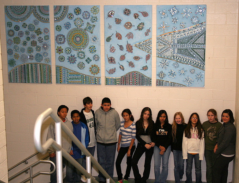 "Some of the student artists who worked on the mosaic ""gems"" gather at the base of their masterpiece.  SSIMS art teacher, Gabrielle Morcate, is pictured on the far right."