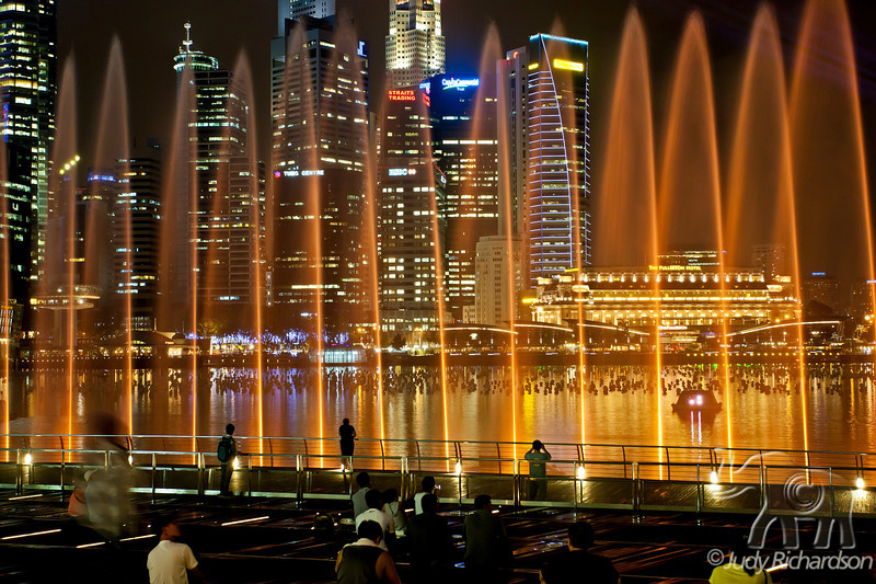 The golden colored of the laser, light, & sound show in the fountain mist of Marina Bay with the city lights of Singapore in the background..