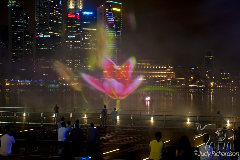 Spectacular colored laser, light, & sound show in the fountain mist of Marina Bay.